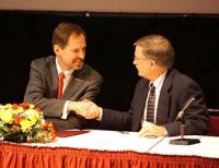 Wickert and Lansdale shake hands during MOU signing